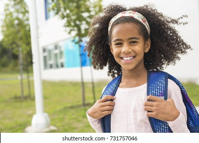 A cheerful african american primary school girl with backpack