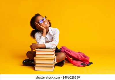 Cheerful African American Schoolgirl Dreaming Sitting At Book Stack Over Yellow Background In Studio. Copy Space