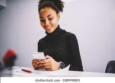 Cheerful african american woman reading good news from income message on cellular sitting at office, smiling dark skinned female student confirming new friend in social network using telephone
