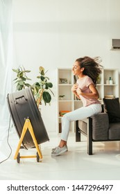 cheerful african american woman sitting in front of blowing electric fan at home