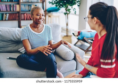 Cheerful african american woman talking with female friend spending time together at apartment, multiracial hipster girls having conversation at home interior, female explaining emotional gesture