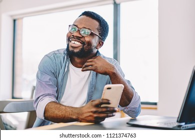Cheerful african american young male smiling holding mobile phone for checking new feed in social networks, happy dark skinned hipster guy looking away laughing at idea for publication in blog