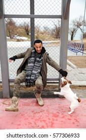 Cheerful african american young man playing with dog and laughing outdoors