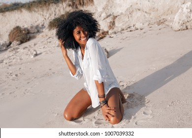cheerful african american young woman having fun on the beach at sunset
