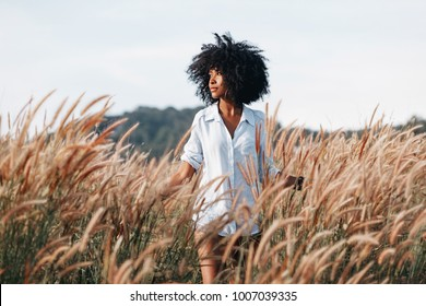 cheerful african american young woman on the field at sunset