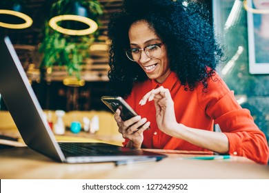 Cheerful African American young woman laughing while reading funny notification on smartphone sitting front laptop computer in cafe. Happy female sending money via online banking app on cellphone