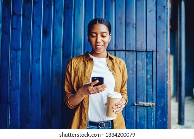 Cheerful African American young woman holding cup of coffee to go and reading message online on mobile phone using 4G internet.Positive dark skinned hipster blogger shopping online via application