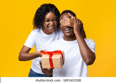 Cheerful african american young woman making Valentine surptise for her happy husband, covering his eyes and holding giftbox, yellow studio background. Valentine celebration concept