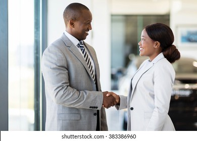 cheerful african car dealer handshake with customer in showroom