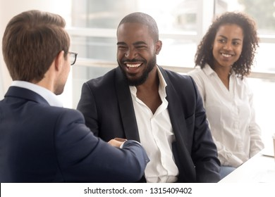 Cheerful african and caucasian colleagues shaking hands greeting each other during briefing, company owner and client handshaking express regard. Business etiquette, first impression and trust concept