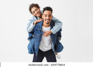 Cheerful african couple in denim shirts having fun together while looking at the camera over grey background