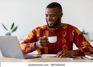 Cheerful African Freelancer Guy Using Laptop And Drinking Morning Coffee At Home, Wearing Traditional Ethnic Shirt, Relaxing At Desk While Working Remotely Online On Computer, Free Space