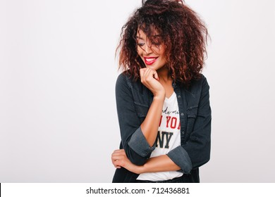 Cheerful african girl with bright make-up posing with shy smile and looking away in front of white wall. Indoor portrait of cute lady with light-brown skin enjoying photoshoot and laughing.