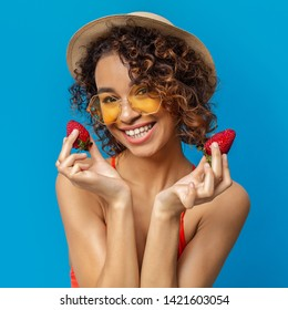 Cheerful african girl in wicker hat and sunglasses holding ripe red strawberries and smiling, blue studio background