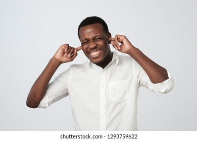 Cheerful african man in white shirt plugging ears with fingers and winking. Guy covering ears and smiling at camera. Do not want to hear concept