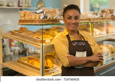 Cheerful African mature woman smiling joyfully posing proudly with her arms folded at her bakery store copyspace baker job occupation businesswoman salesperson retailer professional confidence success