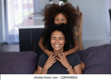 Cheerful african mom and cute kid daughter laughing embracing, mixed race mother with happy little girl hugging playing on sofa, funny black mommy and child having fun enjoying communication at home