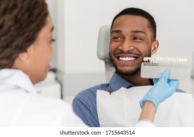 Cheerful african patient and female dentist choosing filling shade, using tooth scale sample