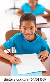 cheerful african schoolboy writing classwork in classroom