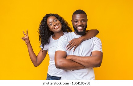 Cheerful african woman hugging her man and showing peace sign, yellow background