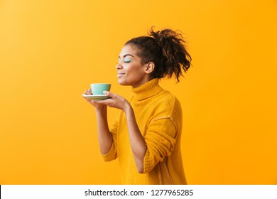 Cheerful african woman wearing sweater holding cup on a saucer isolated over yellow background