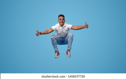 Cheerful African young hipster showing thumb up gesture with both hands and leaping up against blue background