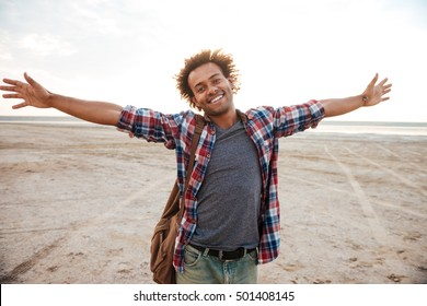 Cheerful african young man with arms spread opened standing at the beach