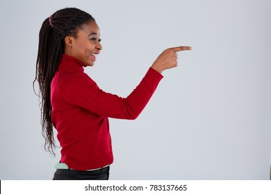 A cheerful African-American gir stands sideways, laughs and twists index finger in front of her.