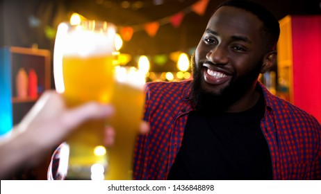 Cheerful african-american male clinking beer glass, enjoying results time in bar