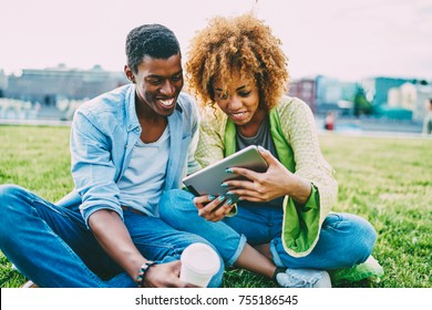 Cheerful afro american best friends watching movie online satisfied with high speed internet connection outdoors,happy couple in love laughing on funny videos on tablet sitting on lawn together