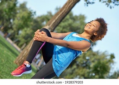 Cheerful Afro American girl doing morning gymnastics outdoors