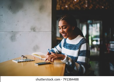 Cheerful afro american hipster girl writing down to do list in notepad while getting message on smartphone.Smiling student doing homework while reading notification with good news on mobile phone