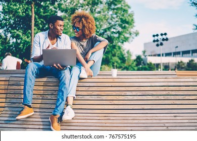 Cheerful afro american male explaining something to attractive female with curly hair during summer conversation at sunny street.Good looking happy best friends laughing while talking outdoor