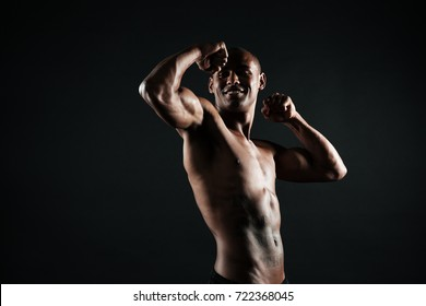 Cheerful afro american sports man showing his biceps, isolated on black background