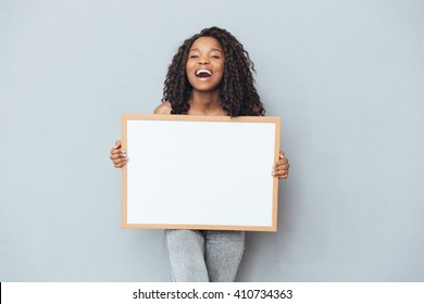 Cheerful afro american woman showing blank board over gray background
