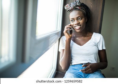 Cheerful afro american woman talking phone and sitting on windowsill