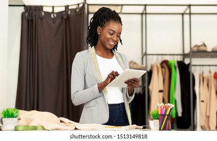 Cheerful Afro Fashion Designer Using Tablet Computer Browsing Internet In Dressmaking Studio. Empty Space
