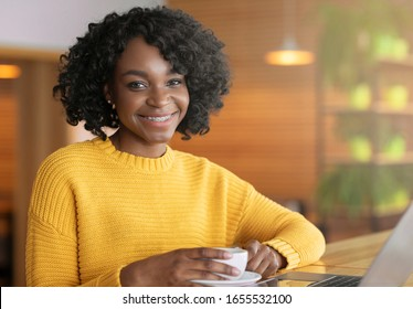 Cheerful afro girl enjoying cup of coffee during lunch break at cafe, empty space