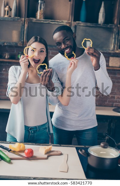 Cheerful afro guy with his wife cooking breakfast and having fun