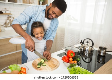 Cheerful Afro Man Showing His Lovely Daughter How To Cut Cucumber, kitchen background, copy space