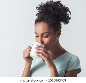 Cheerful Afro-American girl in casual clothes is drinking coffee or tea from a white cup, isolated on white