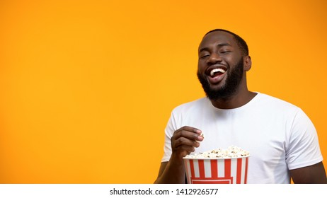 Cheerful Afro-American man eating popcorn and laughing out loud, comedy show