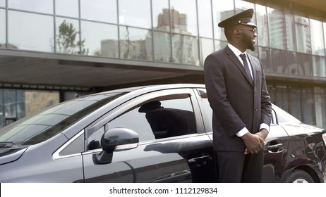 Cheerful Afro-American taxi service driver expecting passengers near luxury car