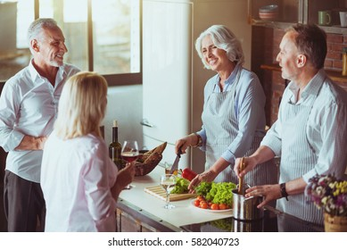 Cheerful aged couples cooking in the kitchen