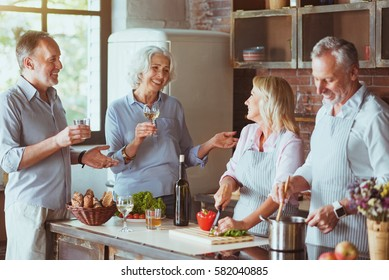 Cheerful aged friends cooking dinner together