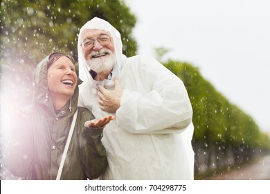 Cheerful aged woman catching raindrops on palms with her laughing husband near by