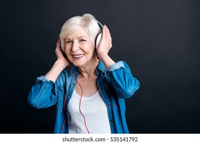 Cheerful aged woman listening to music