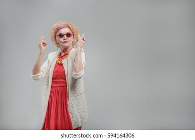 Cheerful aged woman in sunglasses enjoying music