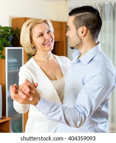 Cheerful aged woman and young boyfriend dancing indoors. Focus on the woman