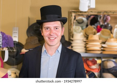 cheerful american adult male shopping in botique and try on cylinder hat
